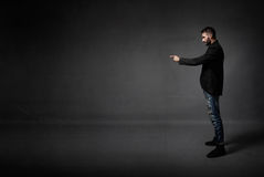 Man indicated empty space. Dark background stock photos