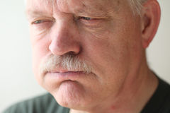 Man with indigestion discomfort. A senior man experiences bloating and reflux from indigestion Stock Images