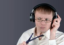 Man indignantly listens to music through headphones. Discontent emotion of a music lover Stock Images