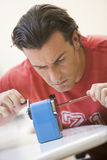 Man indoors using pencil sharpener. On desk stock photography