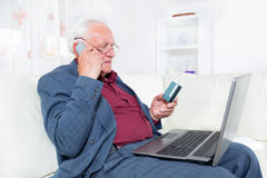 Man indoors using telephone and looking at credit card smiling Royalty Free Stock Photography