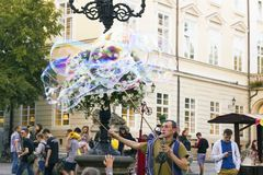 Man inflates big soap bubbles on Market Square. Wiev of city life Stock Photo