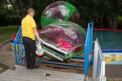 Man inflates zorb with little girl Royalty Free Stock Photo