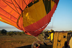 Man Inflating Air Balloon With Hot Air from Firing Nozzle. Fire Blowing Hot Air into Hot Air Balloon royalty free stock image