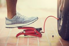 Man Inflating car tyre with foot pump, man put white sport shoes Inflating car tyre with red foot pump in garage in the house stock image