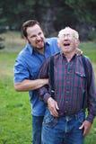 Man inflicting pain on senior. Citizen Stock Photo