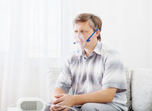 Man Inhaling Through Inhaler Mask Stock Photos