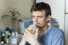 Man Inhaling Through Inhaler Mask Stock Photos