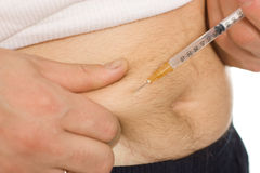 Man inject in the stomach. Man inject with a syringe in his stomach close-up Stock Image