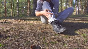 Man injury while jogging in the forest sun, ankle sprain