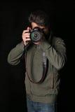 Man inkhaki jacket and jeans takes photo. Close up. Black background Royalty Free Stock Image