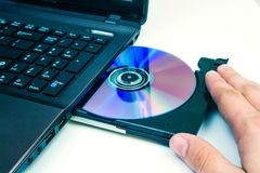 Man insert compact disc Stock Images