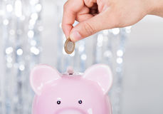 Man Inserting Coin In Piggybank Stock Photography