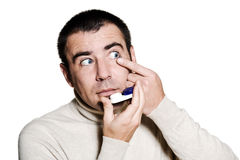 Man inserting a contact lens in his eye Stock Images