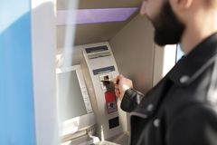 Man inserting credit card into cash machine outdoors. Closeup stock photography