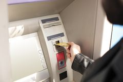Man inserting credit card into cash machine outdoors. Closeup royalty free stock images