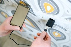 A man is charging the smartphon. A man is inserting a power cord into a USB power supply for charging a smartphone Royalty Free Stock Photo