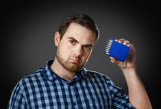 The man inserts to himself into the head the memory card Stock Photos