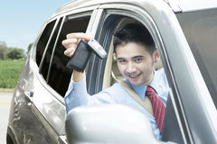 Man inside a car and showing a car key Stock Photography