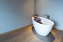 Man inside a luxury bathtub in modern apartment Stock Photography