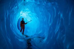 Man inside a melting glacier ice cave. Cut by water from the melting glacier, the cave runs deep into the ice of the Matanuska. Man inside a melting glacier ice royalty free stock photo