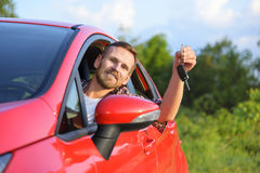 Man inside new red car with keys Royalty Free Stock Images