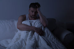 Man with insomnia. Mature man with insomnia sitting in the bed Royalty Free Stock Photos