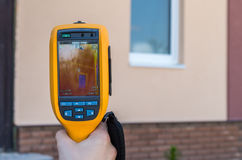Man inspect house window with thermal imaging camera. Infrared inspection of heat loss of window at house Stock Photography