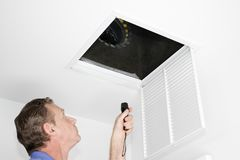 Man Inspecting Air Intake Duct. Male looking up into a ceiling air intake duct with a flashlight checking for maintenance. Person with a flashlight examining royalty free stock photography