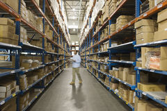 Man Inspecting Boxes In Warehouse Royalty Free Stock Image