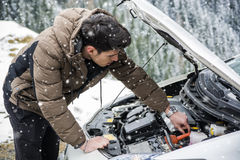 Man inspecting car engine in the snow Royalty Free Stock Photo