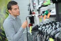 Man inspecting golf clubs. Man inspecting the golf clubs royalty free stock photos