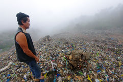 Man Inspecting an Mountain of Trash Stock Photography