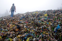 Man Inspecting an Mountain of Trash Royalty Free Stock Image