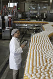 Man inspecting orange juice bottles at bottling plant Stock Images