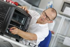 Man inspecting portable oven Stock Photos