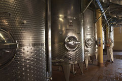 Man Inspecting Wine Vats Inside Winery Stock Photo