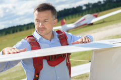 Man inspecting wing glider Stock Images