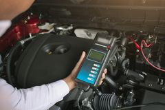 Man inspection holding Battery Capacity Tester Voltmeter. For service maintenance of industrial to engine repair.In Factory transport automobile automotive stock images