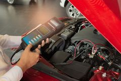 Man inspection holding Battery Capacity Tester Voltmeter.for service. Maintenance of industrial to engine repair.In Factory transport automobile automotive stock image