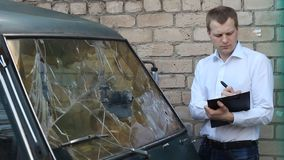 Man inspects a broken car minibus, insurance. Police stock video