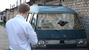 Man inspects a broken car minibus, insurance. Police stock video footage