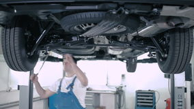 A man inspects the car bottom. An employee checks rail fastening with a stick. Master checks the condition of the car's wheels. The spare wheel is fixed under stock video footage
