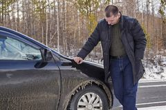 A man inspects the frozen car Royalty Free Stock Photography