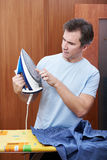 Man inspects a hot iron before ironing Stock Photo