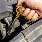 Man inspects the level of oil on car engine dipstick Royalty Free Stock Image
