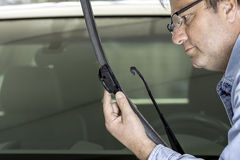 Man inspects a windshield wiper for wear Stock Photos