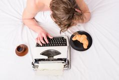 Man inspired lay bedclothes work book. Writer author used old fashioned typewriter. Man with typewriter and coffee lay. Bed. Author guy tousled hair busy write stock image