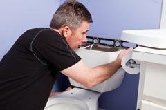 Man installation av behållaren på en ny toalett Arkivbild