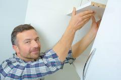 Man installation av handbokstänger för glidning av garderoben i rum royaltyfri foto